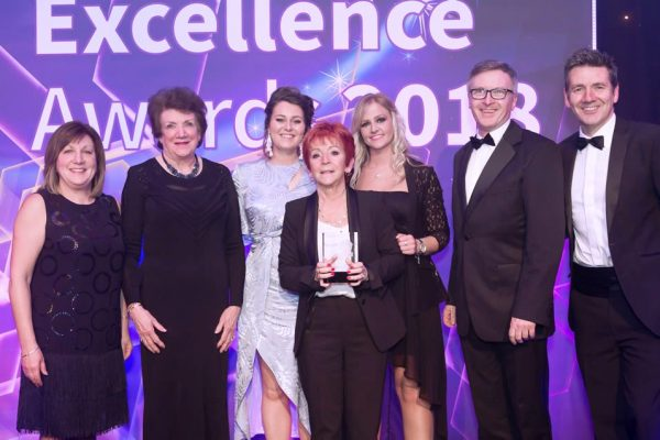 Rossie staff collecting award
