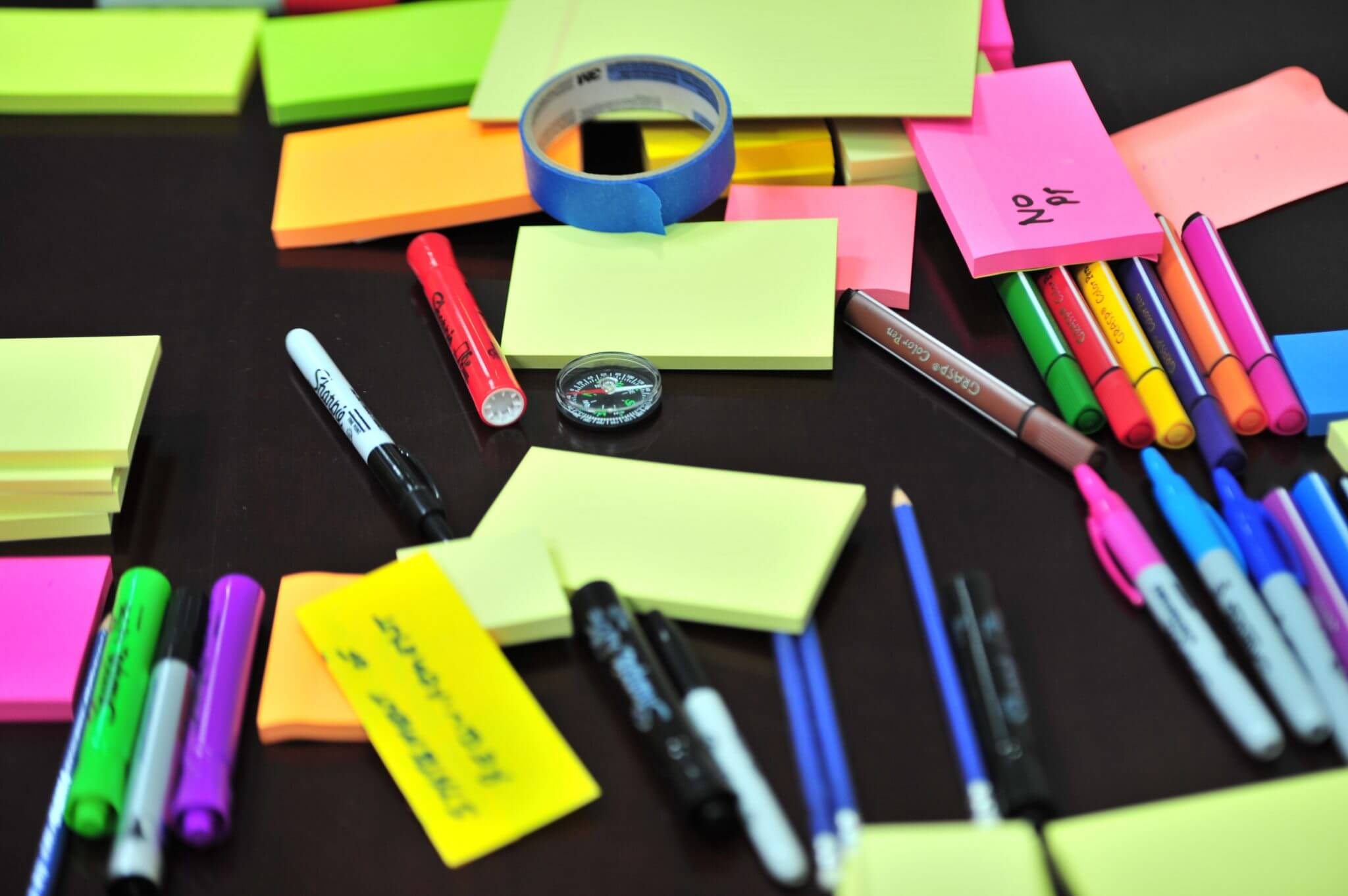 pencils, pens and post it notes spread out on a table