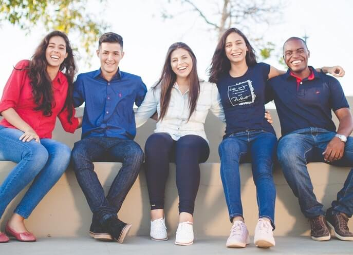 image of students sitting together on a wall